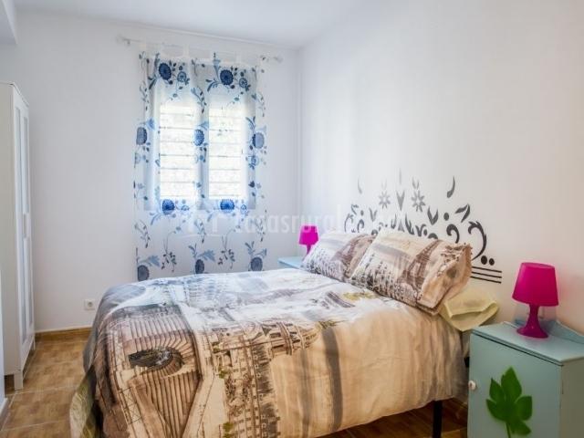 Dormitorio de matrimonio con armario y mesillas lacados en blanco