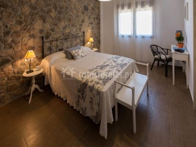 Dormitorio de matrimonio con pared de piedra en la planta baja