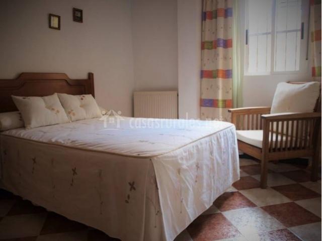 Dormitorio con cama de matrimonio y ventanas