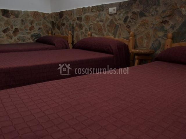 Dormitorio con tres camas con colchas burdeos