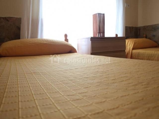 Dormitorio con ventana y colcha