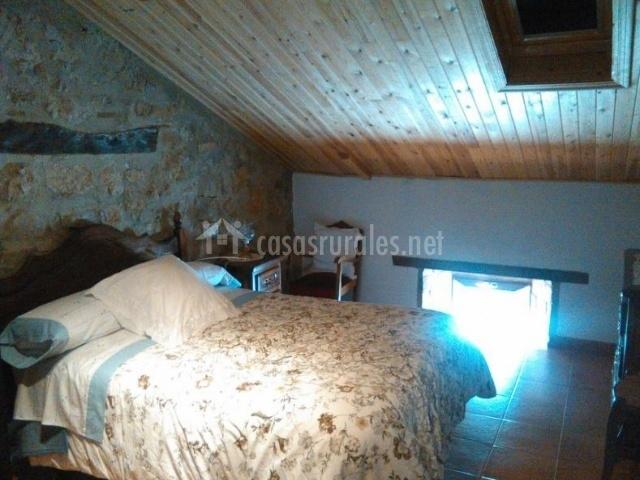 Apto dormitorio de matrimonio con pared de piedra