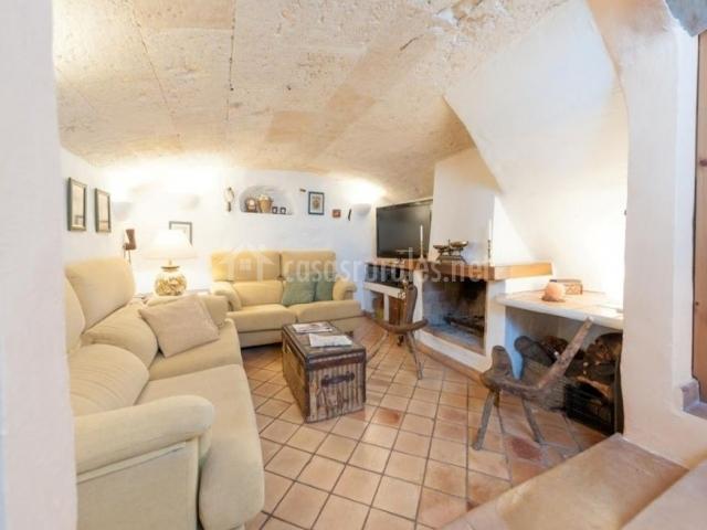 Sala de estar con sillones en tonos crema y chimenea