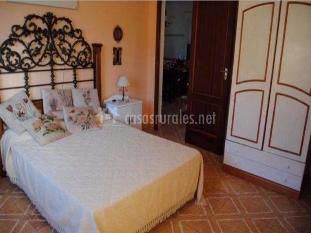 Dormitorio de matrimonio con cabecero tallado y cojines de flores