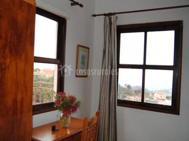 Dormitorio de matrimonio con mesa de madera y silla frente a la ventana