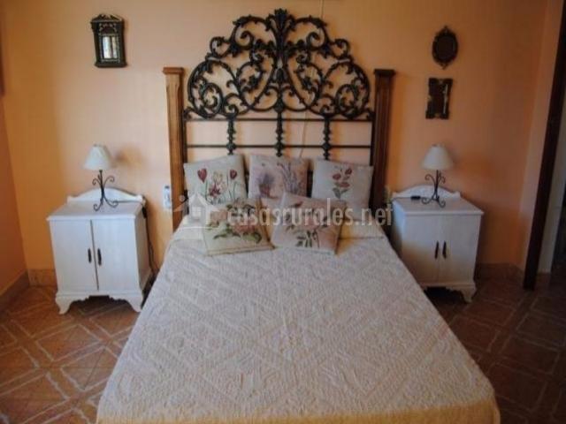Dormitorio de matrimonio con mesillas en color blanco y cojines