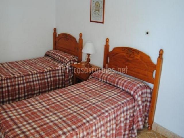 Dormitorio doble con colchas de cuadros y mesilla