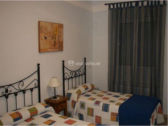 Dormitorio doble de la casa rural con colchas a cuadros