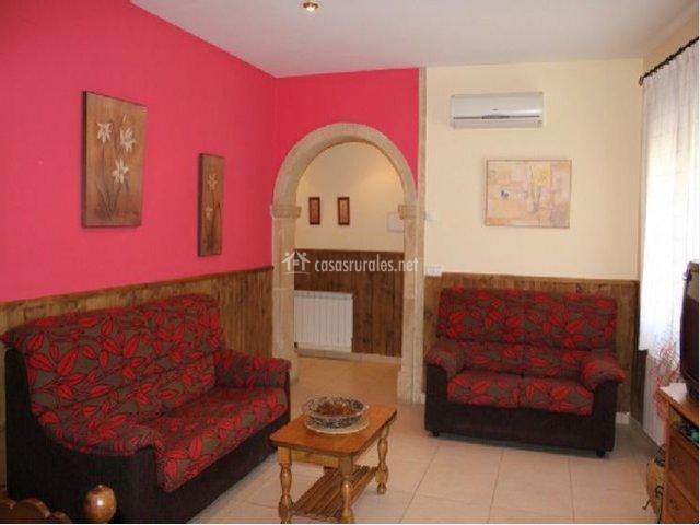 Parte del salón de la casa rural con sofás y pared de color rosa fucsia
