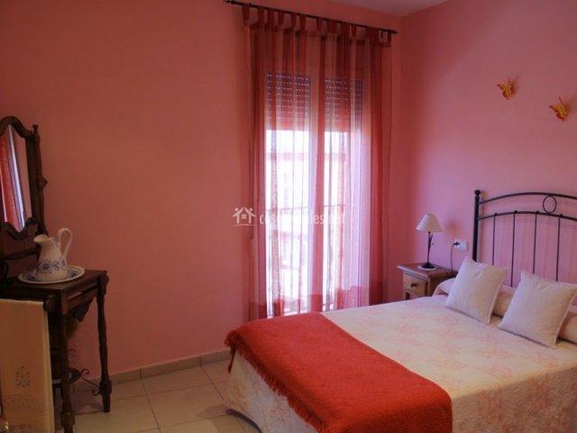 Dormitorio con paredes rosa y lavamanos en la casa rural