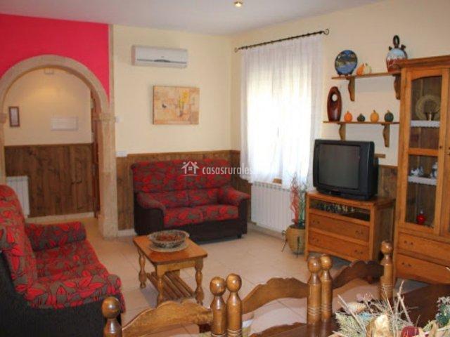 Dos sofás de color rojizo en el salón-comedor de la casa rural
