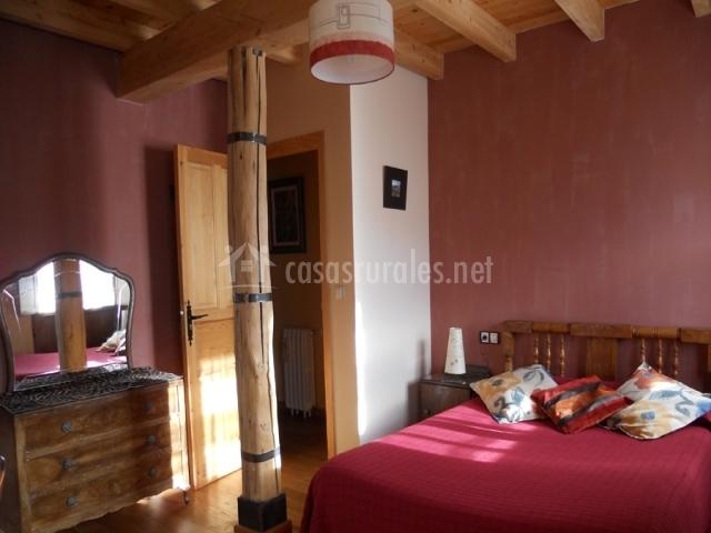 Dormitorio con pilar de madera de la casa rural