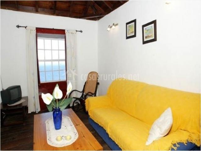 Salón con sofá amarillo en la casa rural
