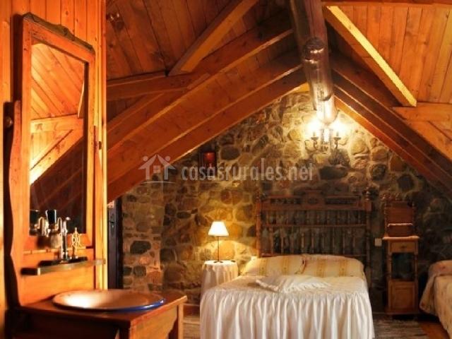Dormitorio con vigas abiertas de madera y muros de piedra