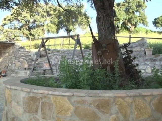 Árbol del jardín junto a columpios del parque infantil