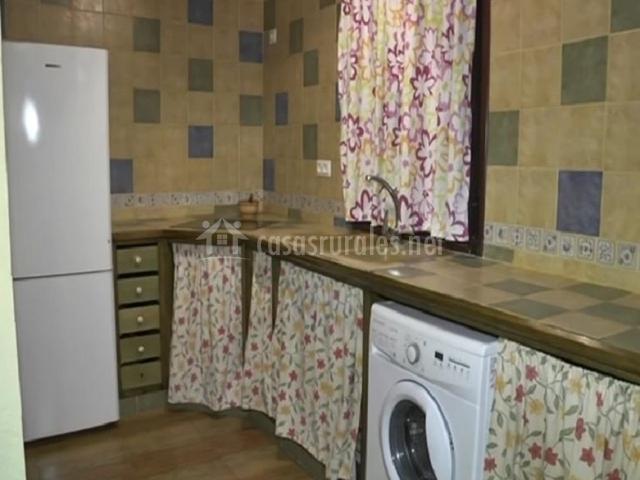 Cocina con encimera esquinada y lavadora