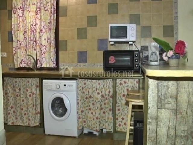 Cocina con microondas colgado y hornillo debajo