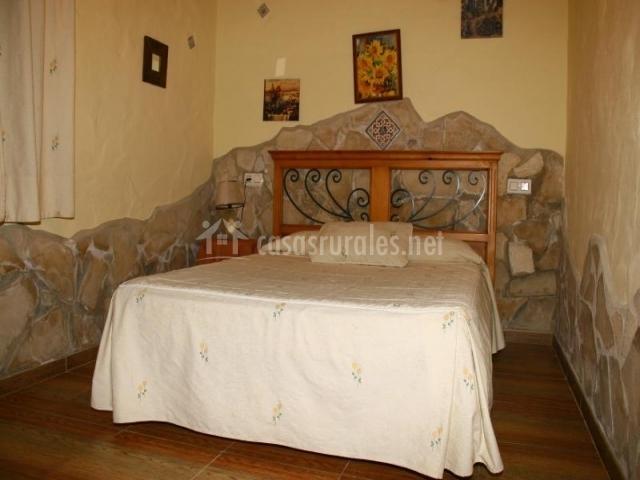 Dormitorio de matrimonio con acabado de piedras en el bajo de las paredes