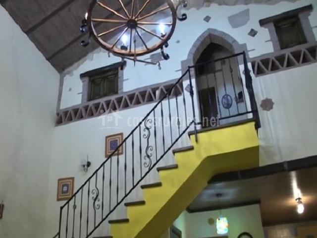 Escaleras amarillas en el salón al primer piso