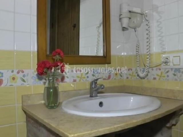 Lavabo de aseo con secador colgado en la pared