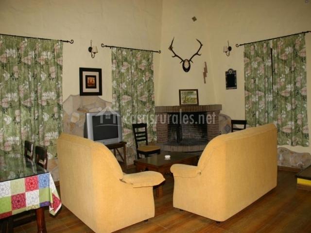 Salón con dos sillones amarillos frente a la chimenea