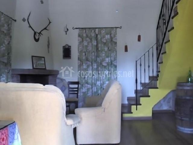 Salón con dos sillones y escaleras amarillas al primer piso