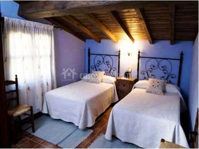 Dormitorio doble blanco con paredes azules y vigas de madera
