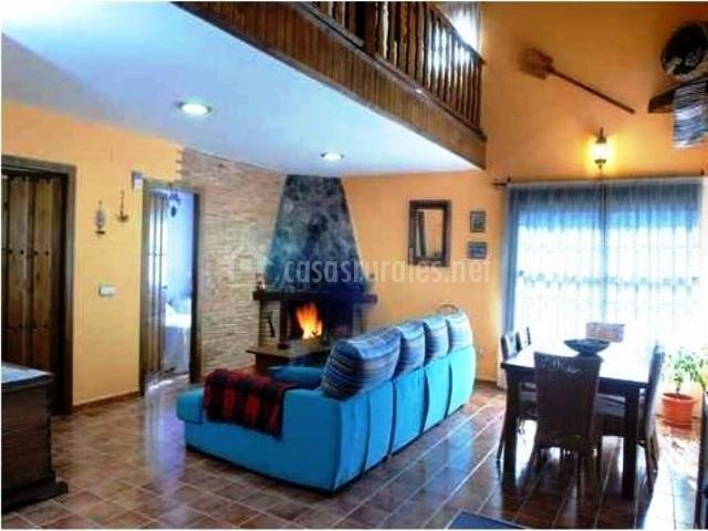 Salón comedor con sillones azules y chimenea de piedra