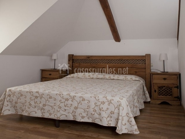 Habitación de matrimonio con cabecero de madera
