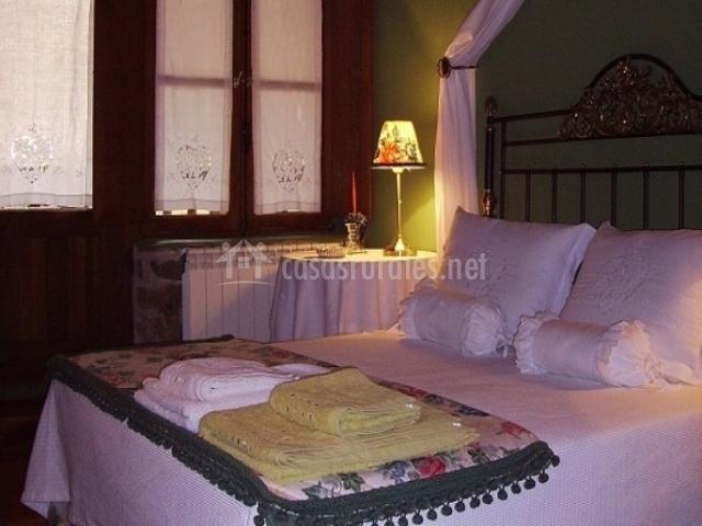 Dormitorio con cama de matrimonio y elegante dosel