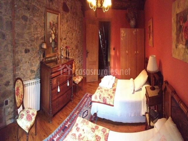 Dormitorio con dos camas y una original pared de piedra
