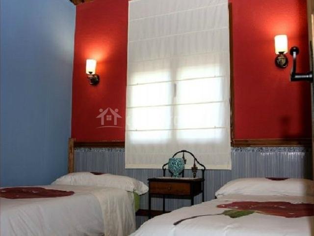 Dormitorio doble con pared burdeos