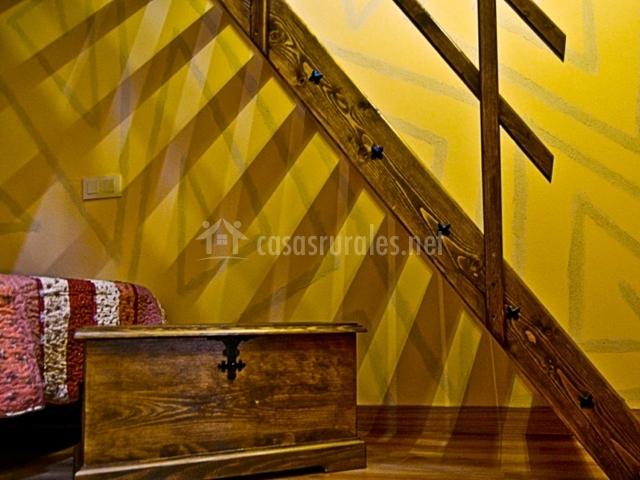 Cama y baúl bajo las escaleras