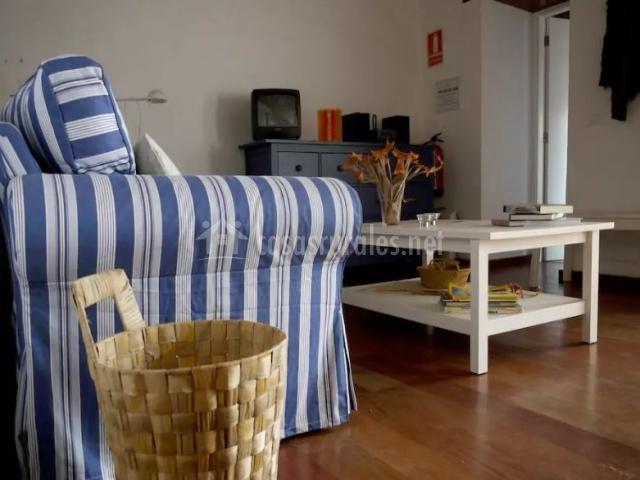 Sala de estar con suelos de madera y revistero