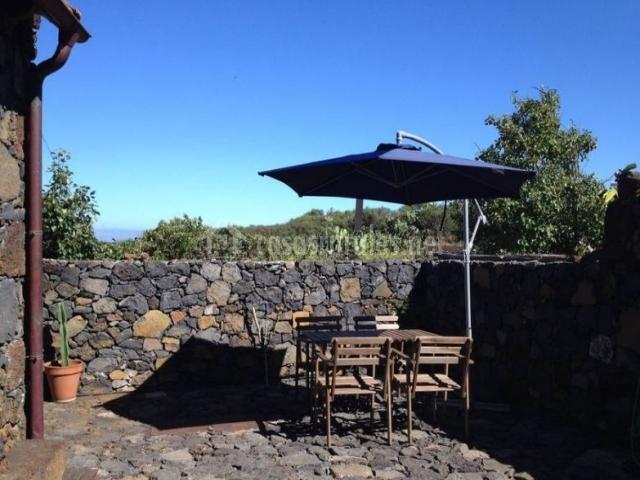 Vistas de la terraza con mesa y sombrilla en el patio