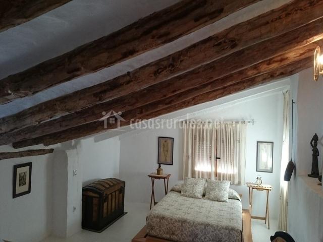 Habitación abuhardillada con vigas de madera en el techo y cama de matrimonio