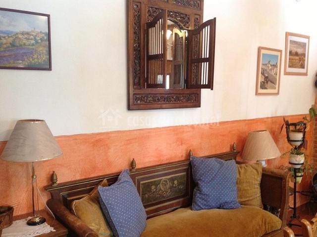 Sofá de la sala de estar con cojines de colores y espejo de madera tallada en la pared