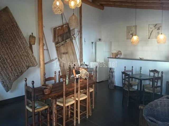 Vista de la bodega con gran mesa de comedor y barra de bar