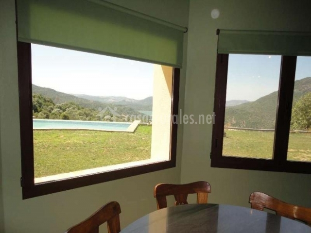 Mesa de comedor con ventana hacia la piscina