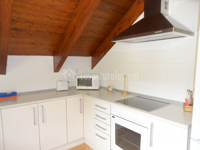 Cocina con horno y microondas y encimera blanca