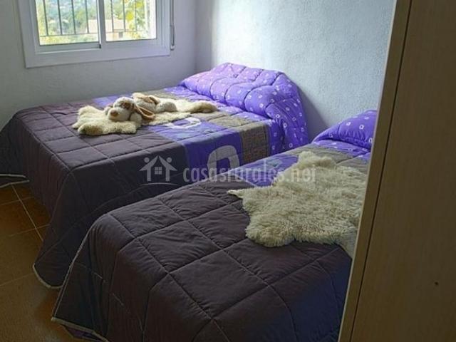 Dormitorio doble con un par de camas individuales y ventana