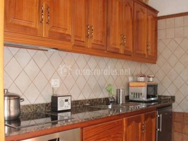 Cocina con armarios de madera y horno bajo la vitro