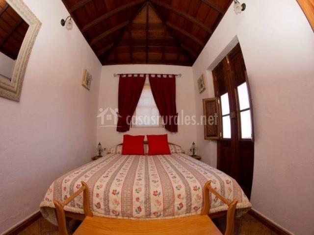 Dormitorio de matrimonio con cojines en color rojo y cortinas en la ventana