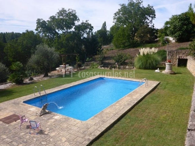 Amplio jardín con piscina repleto de árboles