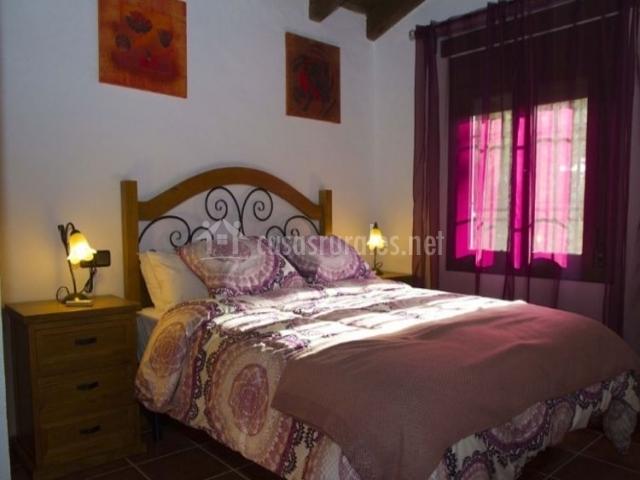 Dormitorio de matrimonio con detalles en morado y madera