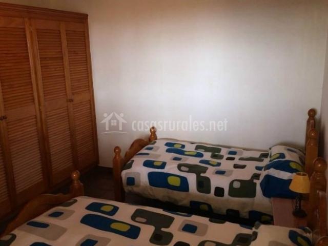 Dormitorio doble con camas individuales y detalles en azul