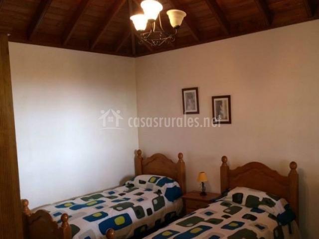 Dormitorio doble con camas individuales y techos de madera