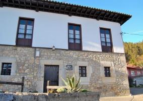 Fachada con muro de piedra y ventanas de madera