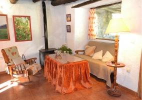 Salon con ventanal y chimenea en la caasa rural