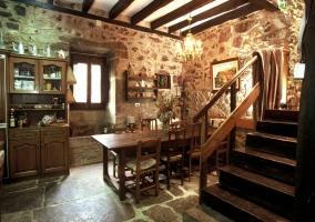 Comedor con paredes de piedra y escaleras